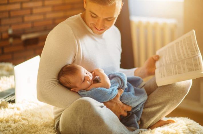 Dad and baby - dad reading book to baby and smiling. Dad and baby bonding