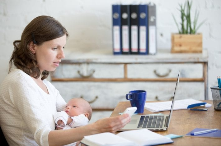 newborn - new mother working at computer with phone and coffee