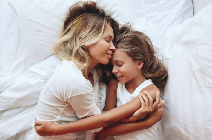 Mother and daughter cosleeping hugging and smiling