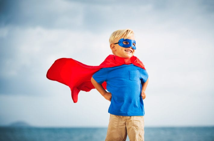 Young boy standing in a superhero pose