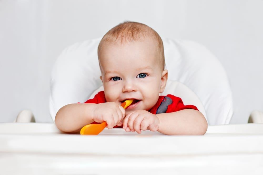 weaning - first foods - early weaning - wean baby - baby holding spoon and smiling