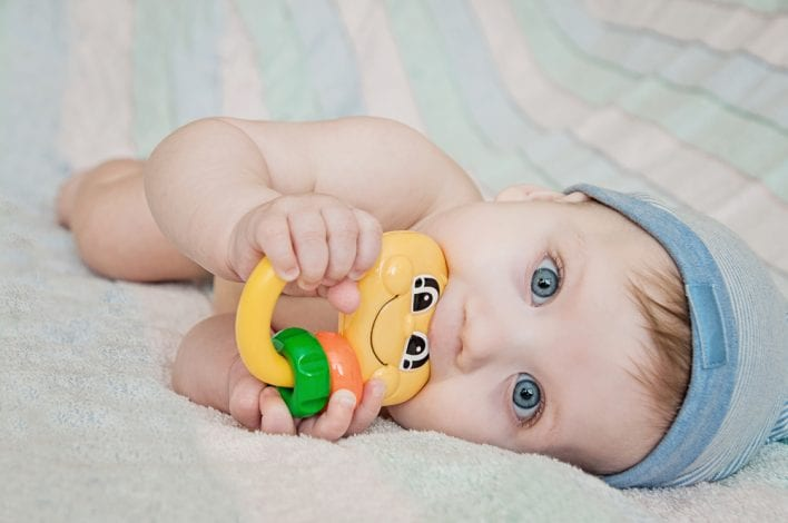 baby holding toy and biting down - baby teething