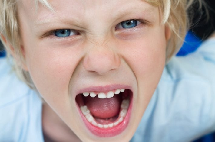 boy aggressively shouting child lashes out