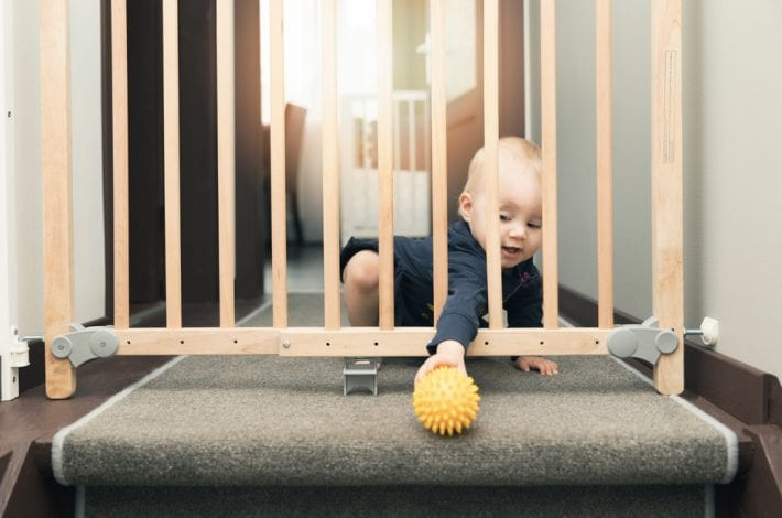 child next to stairgate baby proofing