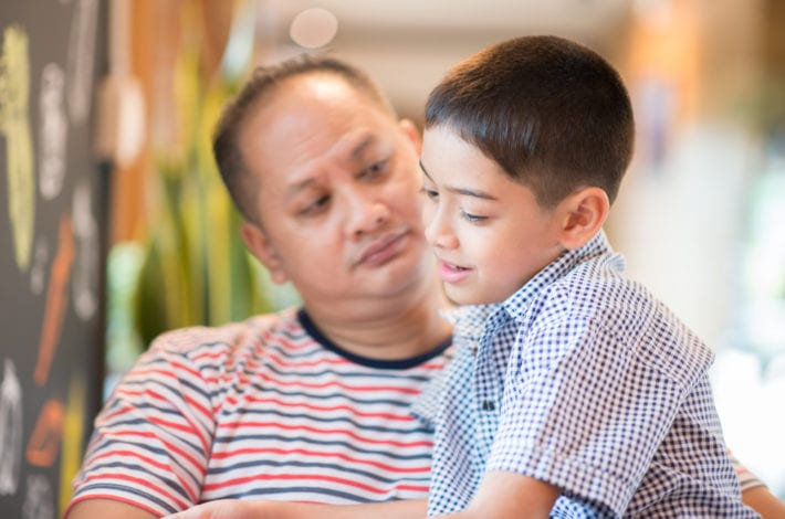 father and son sitting and talking together. Father listening