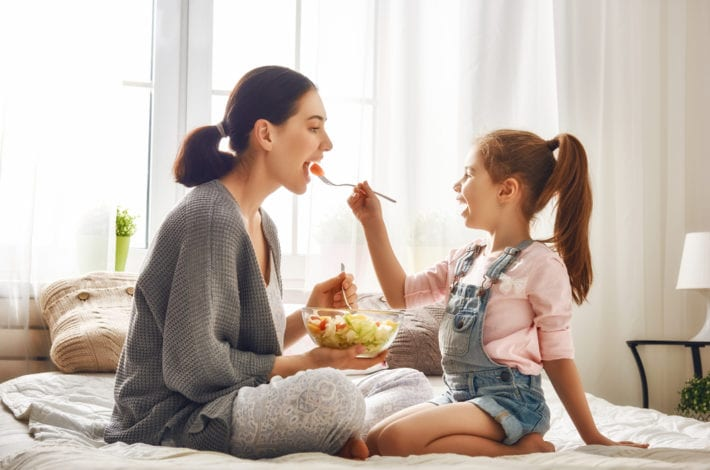 mother eating healthily - fed fruit salad by daughter