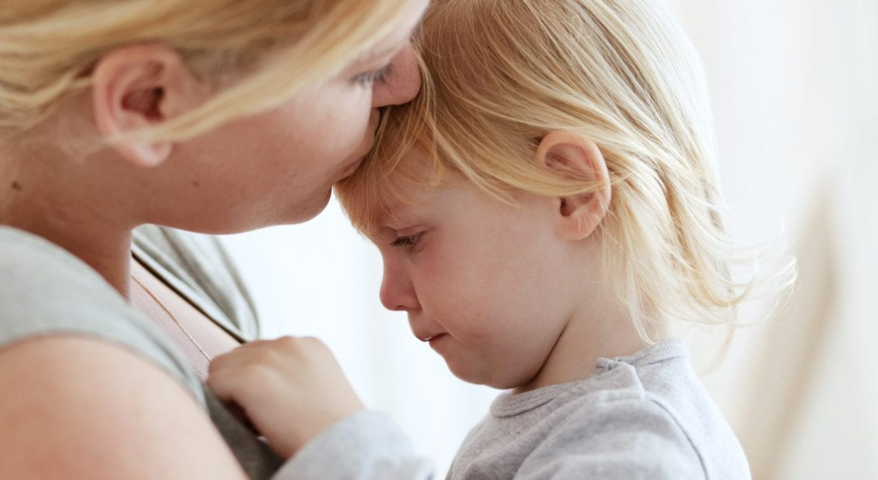 mother kissing crying toddler on forehead - managing terrible twos