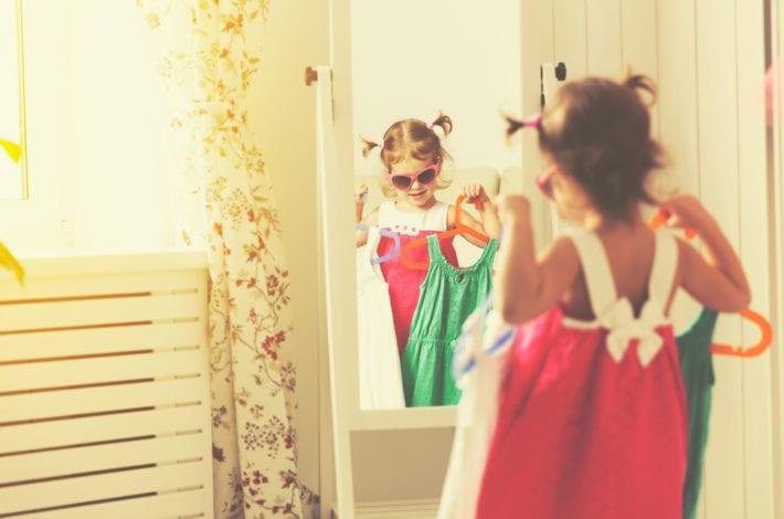 toddler choosing between two dresses