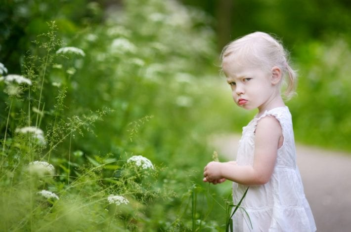 toddler girl looking grumpy and moody terrible twos