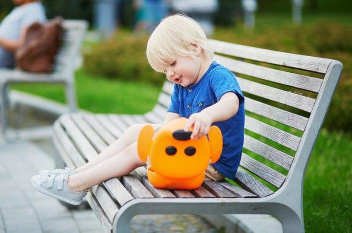 toddler having snack on park bench
