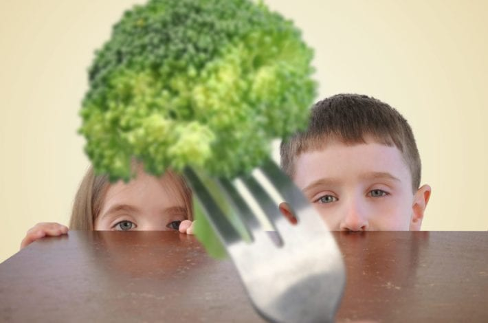 two children looking at a piece of broccoli suspiciously