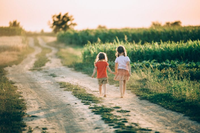 two sisters walking down a path together holding hands