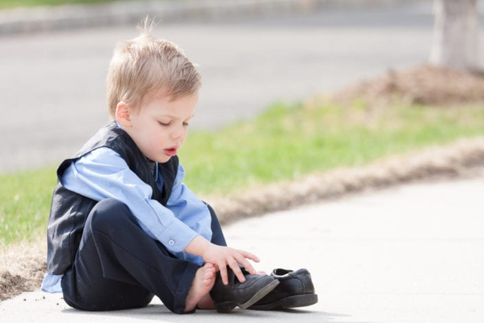 young boy trying to put on his shoes