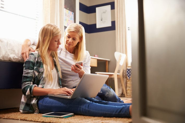 child safe online - mother guiding her teenage daughter on how to use the internet safely