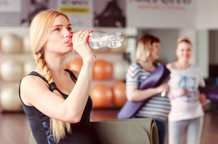 exercising during pregnancy - tips for staying safe -pregnant woman drinking water after a class